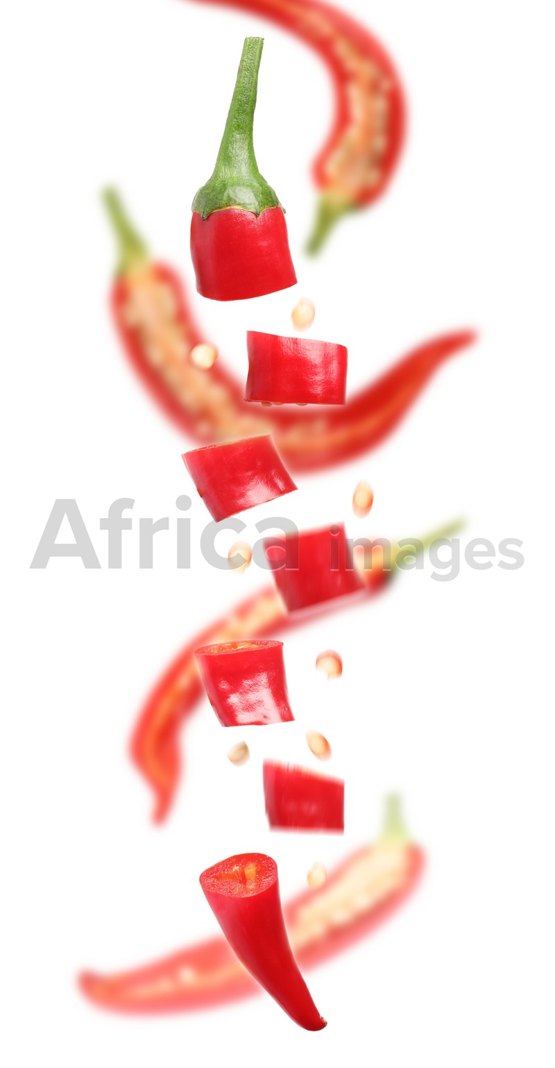 Pieces of ripe red chili peppers falling on white background. Vertical banner design