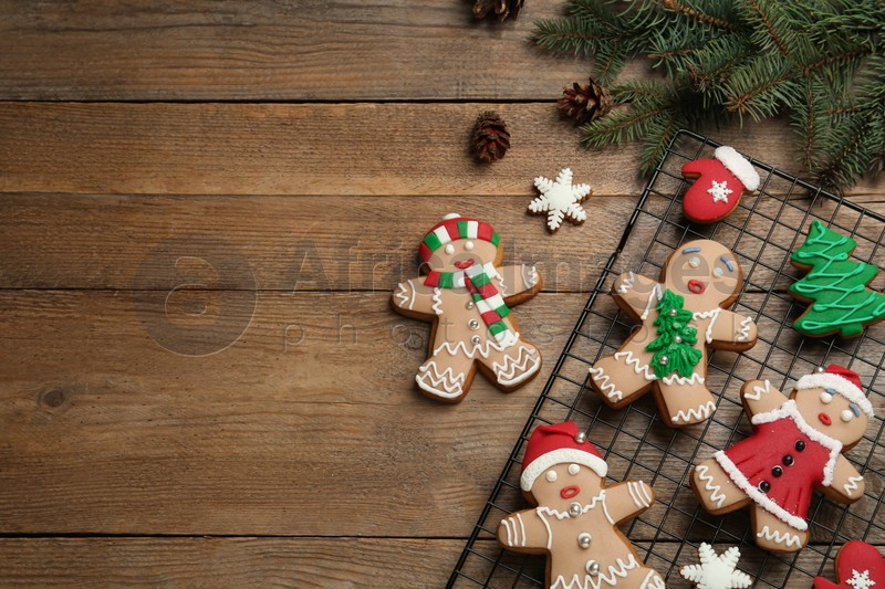 Delicious Christmas cookies and fir branches on wooden table, flat lay. Space for text