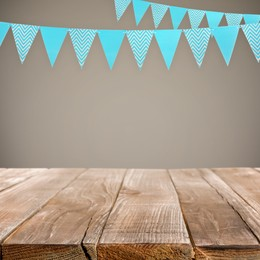 Empty wooden table and decorative bunting flags hanging on beige wall