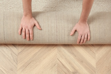 Man rolling out new carpet flooring indoors, top view. Space for text