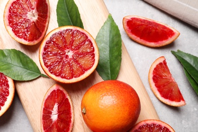 Ripe red oranges, green leaves and wooden board on light table, flat lay
