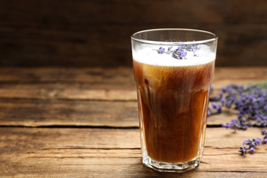 Delicious coffee with lavender on wooden table. Space for text