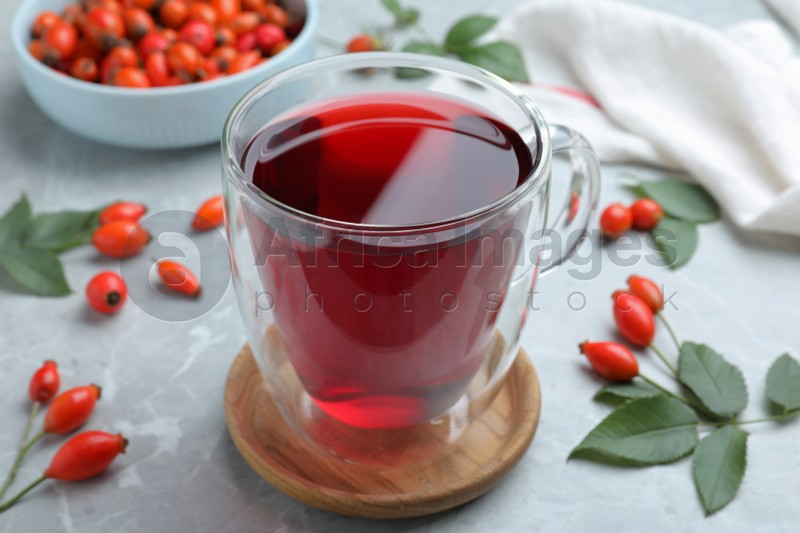 Aromatic rose hip tea and fresh berries on light grey marble table, closeup