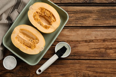 Halves of fresh spaghetti squash in baking dish on wooden table, flat lay with space for text. Cooking at home