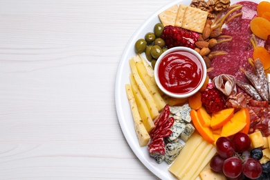 Plate of different appetizers with sauce on white wooden table, top view. Space for text