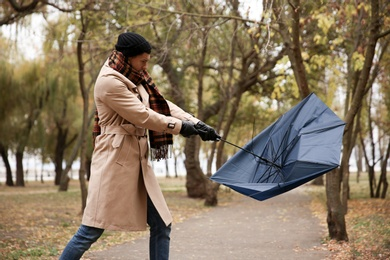 Man with blue umbrella caught in gust of wind outdoors