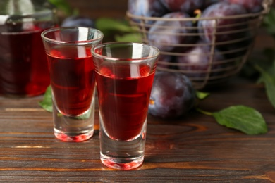Delicious plum liquor on wooden table. Homemade strong alcoholic beverage