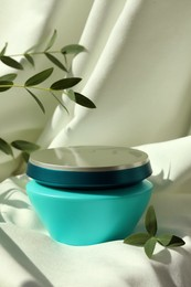 Jar of hair care cosmetic product and green leaves on light fabric