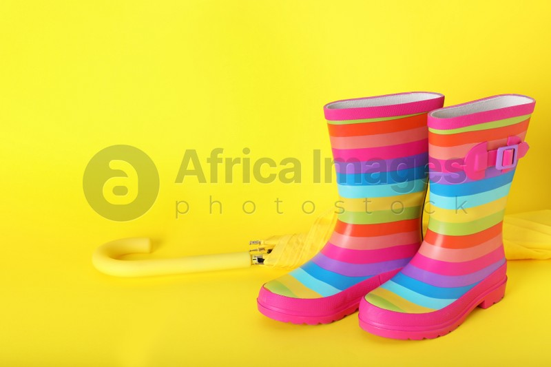 Pair of striped rubber boots near umbrella on yellow  background. Space for text