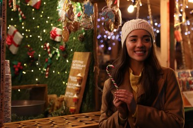 Young woman spending time at Christmas fair, space for text