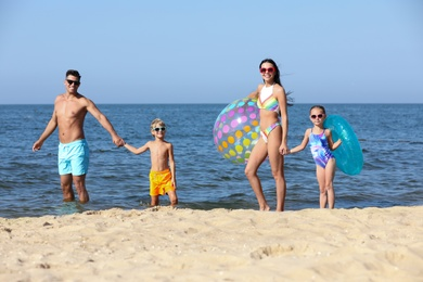 Happy family with inflatable ball and ring in sea. Summer holidays