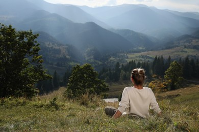 Woman enjoying beautiful mountain landscape, back view. Space for text
