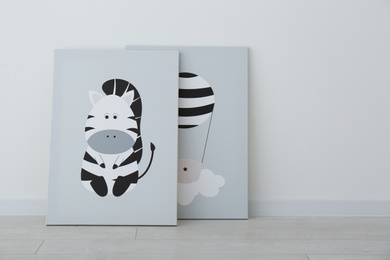 Adorable pictures of zebra and air balloon on floor near white wall. Children's room interior elements