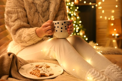 Woman with cup of hot drink and cookies near Christmas tree at home, closeup