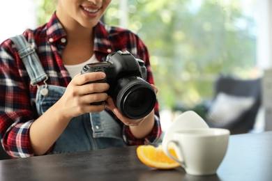 Young photographer taking picture of cups at table indoors, closeup