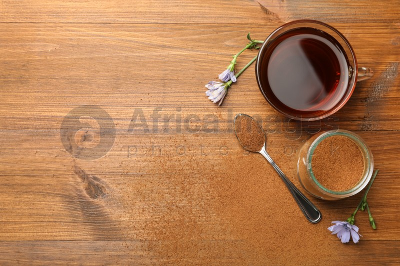 Cup of delicious chicory drink, powder and flowers on wooden table, flat lay. Space for text