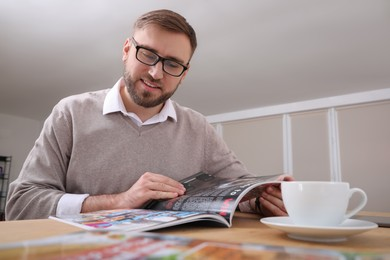 Young man reading modern magazine at table indoors