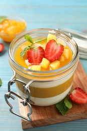 Delicious panna cotta with mango coulis and fresh fruit pieces on light blue wooden table