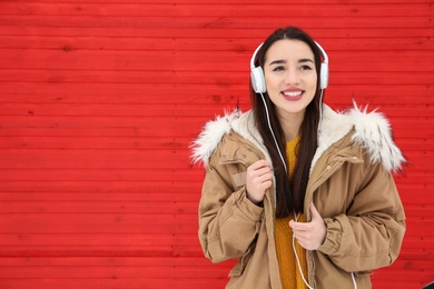 Beautiful young woman listening to music with headphones against color wall. Space for text