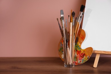 Easel with empty canvas and art supplies on wooden table. Space for text