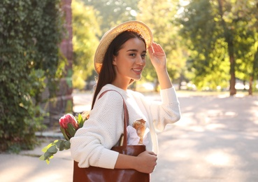 Young woman with leather shopper bag in park