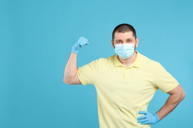 Man with protective mask and gloves showing muscles on light blue background, space for text. Strong immunity concept