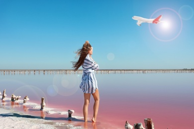 Beautiful woman near pink lake and airplane in sky on background. Summer vacation