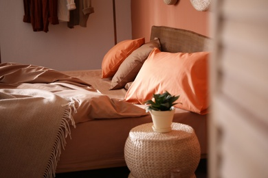 Bed with orange and brown linens in stylish room