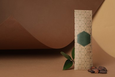 Scented sachet, leaf and cocoa beans on brown background, space for text