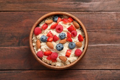 Tasty oatmeal porridge with berries and almond nuts in bowl on wooden table, top view