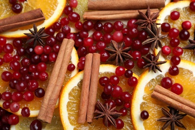 Fresh ripe cranberries, spices and orange slices as background, closeup