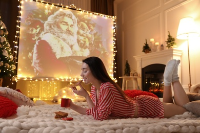 MYKOLAIV, UKRAINE - DECEMBER 24, 2020: Woman watching The Christmas Chronicles movie via video projector in room. Cozy winter holidays atmosphere