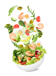 Fresh ingredients for tasty salad falling into bowl on white background
