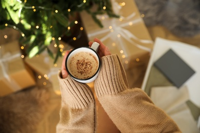 Woman holding cup of cocoa indoors, above view. Christmas mood