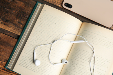 Book, headphones and smartphone on wooden table, closeup