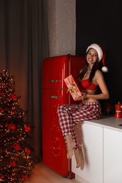 Beautiful woman in Santa hat with Christmas gift in kitchen