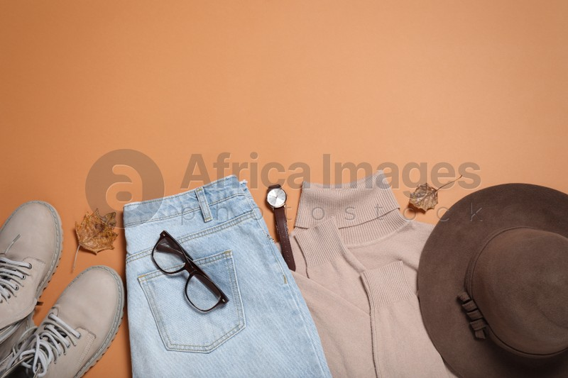 Flat lay composition with stylish hat and clothes on orange background, space for text