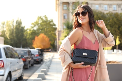Young woman in sunglasses with stylish black bag on city street