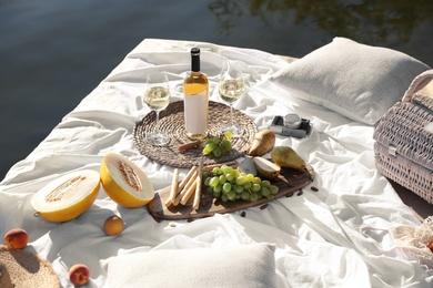 Picnic blanket with delicious food and wine on pier