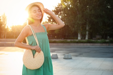 Young woman with stylish straw bag outdoors. Space for text