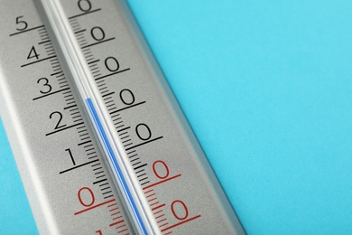 Weather thermometer on light blue background, closeup. Space for text