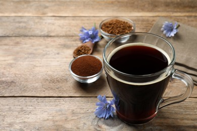 Glass cup of delicious chicory drink and flowers on wooden table. Space for text