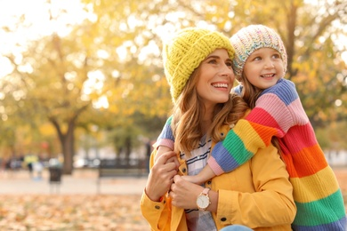 Mother with her cute daughter spending time together in park. Autumn walk