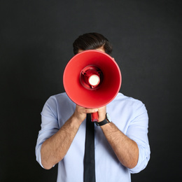 Man with red megaphone on black background