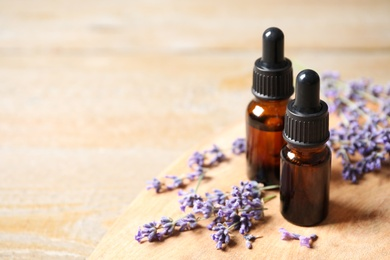 Bottles of essential oil and lavender flowers on wooden table. Space for text