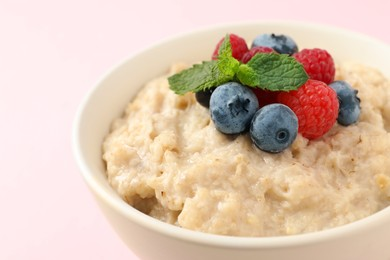 Tasty oatmeal porridge with raspberries and blueberries in bowl on light background, closeup