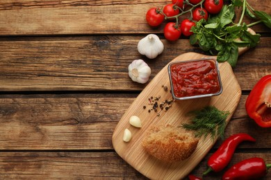 Delicious adjika sauce in bowl with bread and ingredients on wooden table, flat lay. Space for text