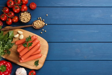 Fresh raw vegetarian sausages, soybeans and vegetables on blue wooden table, flat lay. Space for text