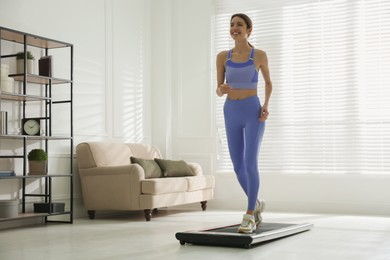 Sporty woman training on walking treadmill at home