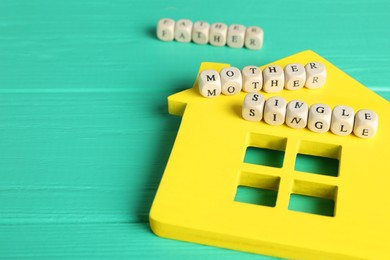 House model and cubes with text Single Mother on turquoise wooden table, closeup